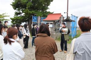 閖上の震災前の姿や被災直後の様子を写真を使って説明する長沼さん=名取市閖上の日和山